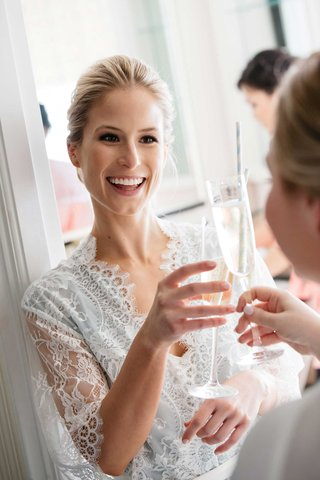 bride-toasting-bridesmaid-in-lace-robe-with-champagne-flute-and-straw