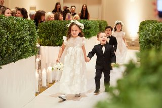 wedding-ceremony-flower-girl-in-vintage-inspired-dress-ring-bearer-in-tuxedo-holding-hands-greenery