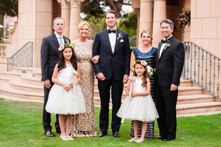 groom-in-tuxedo-with-family-champagne-dress-and-flower-girls-in-short-white-dresses-wands