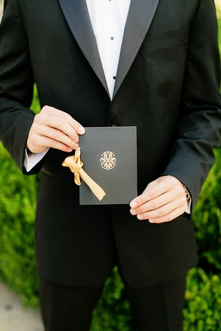 black-ceremony-program-with-gold-monogram-tied-with-gold-ribbon
