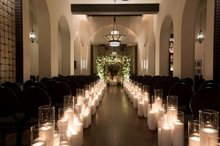 hotel-figueroa-wedding-ceremony-long-aisle-with-candles-in-hurricane-vases-greenery-white-flower-arc