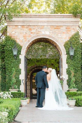 bride-and-groom-kiss-during-wedding-portrait-backs-to-camera-tuxedo-villa-venue-in-arizona-wedding