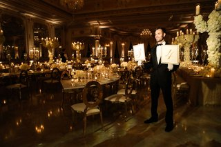 man-in-tuxedo-holding-table-number-signs-leading-guests-to-their-table-wedding-ideas