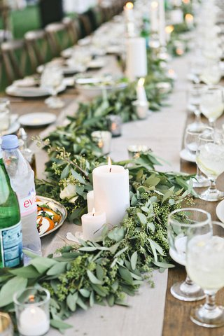 farm-wedding-reception-table-with-leafy-garlands-pillar-candles-on-a-tan-runner
