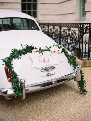 wedding-ceremony-just-married-getaway-car-with-wreath-garland-and-fresh-flowers-on-back-classic-car