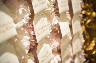 wedding-reception-envelope-escort-cards-names-in-gilt-calligraphy-pinned-to-white-pink-peonies