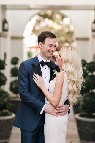 bride-in-sleeveless-wedding-dress-ivory-with-groom-in-navy-suit-smiling-laughing-long-blonde-hair