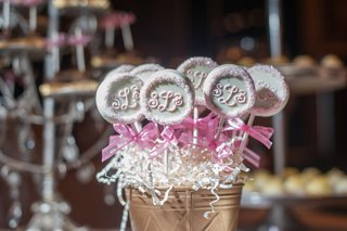 wedding-reception-dessert-table-with-the-couples-monogram-on-pastry-pops-in-a-golden-bucket