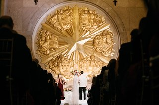 the-hall-of-state-at-fair-park-wedding-ceremony-gold-star-at-altar-decor-minimal-decorations