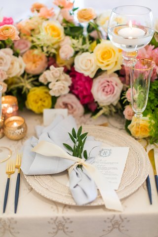 wedding-guest-place-setting-intricate-charger-plate-with-menu-light-blue-napkin-tied-sprig-of-greens
