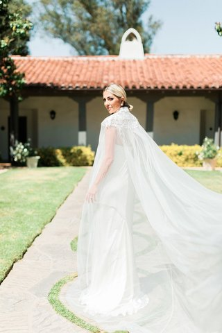 bride-with-low-ponytail-in-slim-sheath-dress-paired-with-long-cape