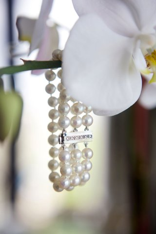 white-phalaenopsis-orchid-with-three-strand-pearl-bracelet-hanging-from-it-wedding-jewelry