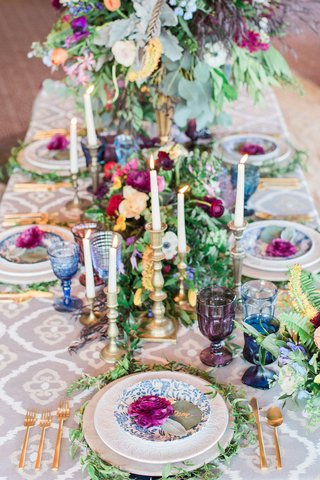 colorful-centerpieces-with-gold-and-silver-candlesticks-maroon-flowers-greenery-colored-glassware