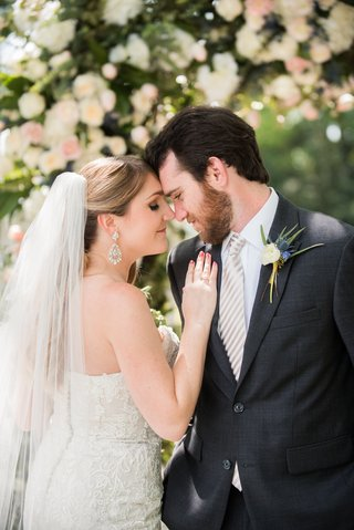 bride-in-lace-dress-groom-in-charcoal-suit-and-white-satin-tie-pose-with-foreheads-touch