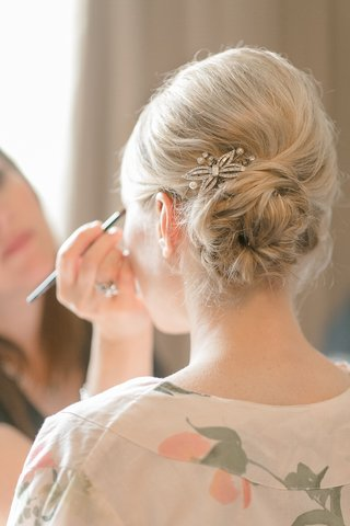 bride-in-an-off-white-robe-with-pink-flowers-side-bun-with-a-crystal-and-pearl-hair-pin