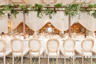 wedding-reception-long-table-wood-cane-chairs-and-arbor-overhead-drapery-greenery-french-garden