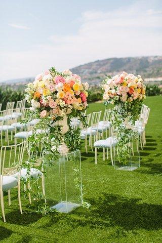 wedding-ceremony-laguna-niguel-acrylic-riser-pink-orange-yellow-flower-arrangements-light-blue-chair