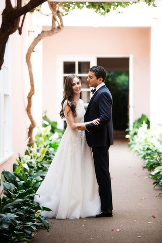 skirball-cultural-center-wedding-bride-in-sabrina-dahan-wedding-dress-groom-in-tuxedo-smiling
