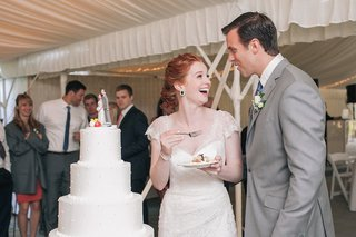 bride-and-groom-standing-next-to-round-white-cake