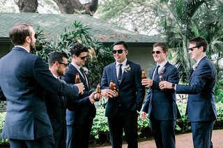 groom-and-groomsmen-in-suits-and-sunglasses-with-bottles-of-beer-hawaii-wedding-preparation