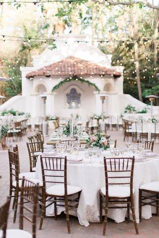 wedding-reception-courtyard-bistro-lights-wood-chair-white-linen-green-pink-flower-centerpieces