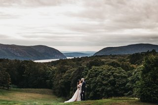 bride-and-groom-in-front-of-sweeping-views-of-field-trees-lake-and-hills