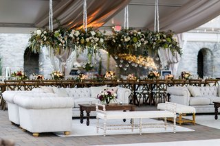 wedding-reception-head-table-flower-chandelier-lounge-areas-chesterfield-sofas-tufted-wood-tables