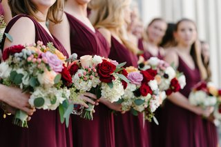 bridesmaids-in-burgundy-dresses-with-colorful-bouquets-red-pink-white-and-greenery