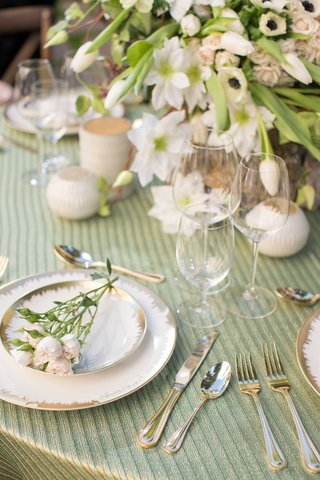white-and-gold-charger-plates-with-pink-and-green-flowers-green-table-linens-white-candles