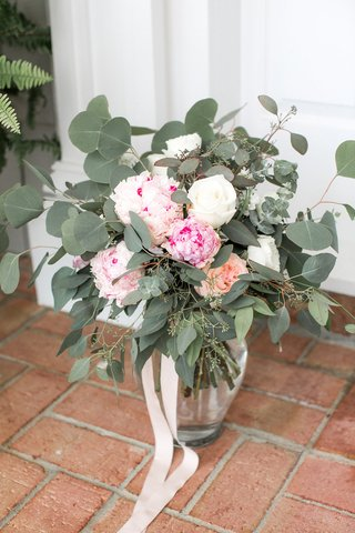 clear-vase-tied-with-ribbon-filled-with-pink-peony-pink-garden-rose-white-rose-eucalyptus-leaves