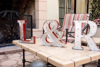 silver-and-red-light-up-marquee-letters-in-bride-and-grooms-initials-ampersand