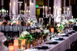 long-wedding-reception-tables-with-crystal-candelabra-greenery-white-flowers-feathers-black-napkins