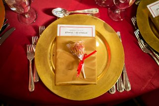 red-and-gold-cake-pop-placed-on-gold-place-setting-red-linen-at-wedding-reception