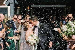 guests-throw-confetti-newlyweds-kiss-outside-church-ceremony-green-maine-wedding-veil-classic-tuxedo