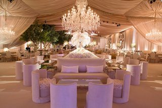tent-wedding-reception-with-plush-furniture-and-chandeliers
