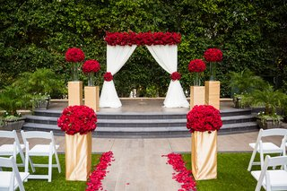 red-roses-on-gold-wrapped-bases-white-drapery-aisle