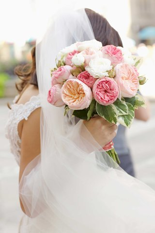 bride-in-veil-and-lace-dress-holding-bouquet-of-pink-garden-rose-flowers-and-white-flowers-greenery