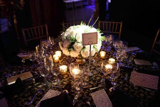 wedding-reception-table-with-a-centerpiece-of-white-roses-with-greenery-surrounded-by-votive-candles