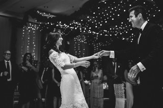 black-and-white-photo-of-bride-and-groom-first-dance-marchesa-dress-twinkle-lights-garlands