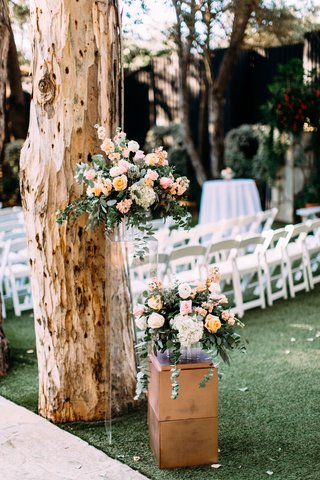 wedding-ceremony-tall-tree-with-lucite-riser-holding-peach-pink-flower-arrangement-greenery