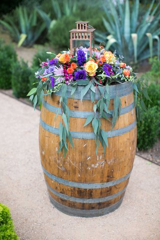 colorful-floral-arrangement-with-berry-tones-of-pink-purple-orange-yellow-and-green-on-wine-barrel