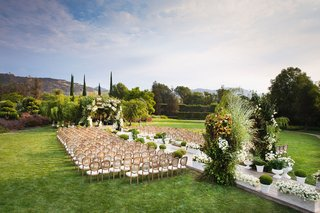 wedding-ceremony-westlake-village-green-lawn-wood-chairs-green-arches-white-flowers