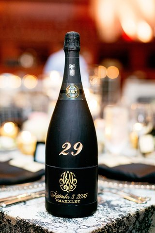 black-bottle-of-champagne-marks-table-number-at-wedding-reception