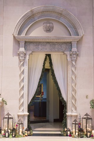 building-arch-ceremony-space-greenery-lanterns-art-institute-of-dayton-wedding-venue-marble-columns