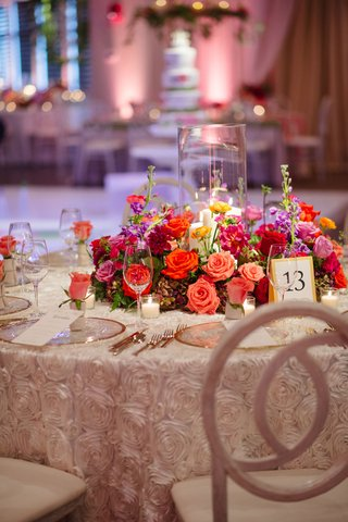 rosette-pattern-linens-white-chairs-gold-charger-plates-pink-orange-red-flowers-around-hurricane