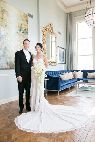 bride-in-rivini-wedding-dress-with-long-train-groom-in-tux-and-white-neck-tie