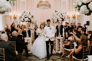wedding-ceremony-ballroom-white-pink-rose-hydrangea-flowers-flower-petal-toss-guests-in-gold-chairs
