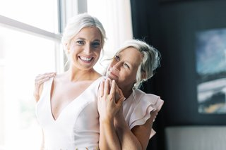 mother-of-the-bride-with-blush-flutter-sleeve-dress-hugging-bride-in-v-neck-from-behind