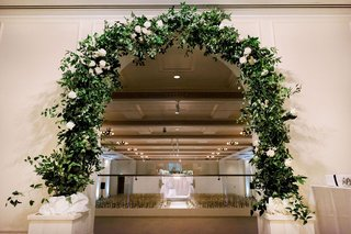 entrance-to-wedding-ceremony-with-arch-of-greenery-and-a-few-white-flowers