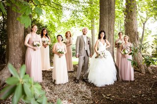 a-bride-and-her-bridal-party-including-bridesmaids-and-a-bridesman-pose-in-the-woods-with-bouquets